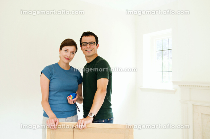 A couple putting up a picture.