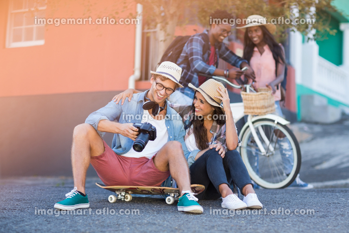 Couple sitting on road interacting with each otherの販売画像