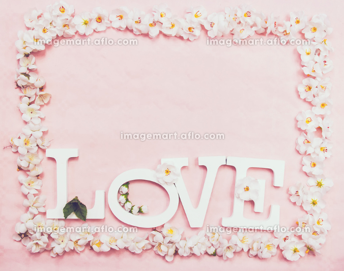 Love word and a floral frame against a pink background
