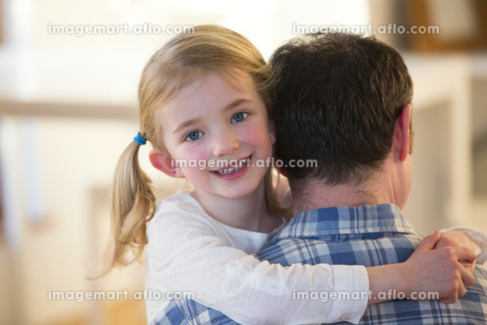 Little girl smiling whilst hugging fatherの販売画像