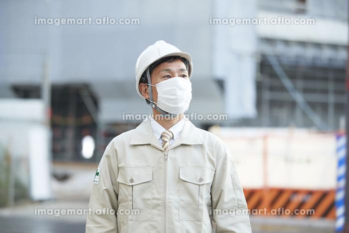 マスクをする作業着の日本人男性の販売画像