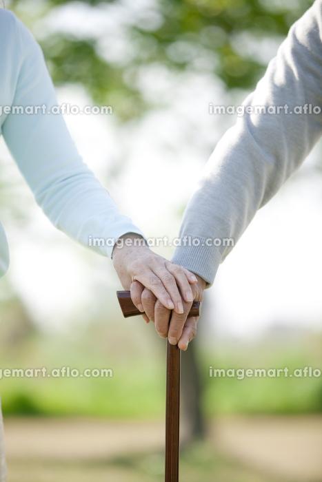杖を持つシニア夫婦の手