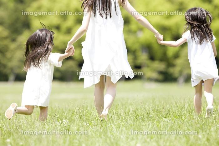 手を繋いで走る大人の女性と2人の子供の後姿の販売画像