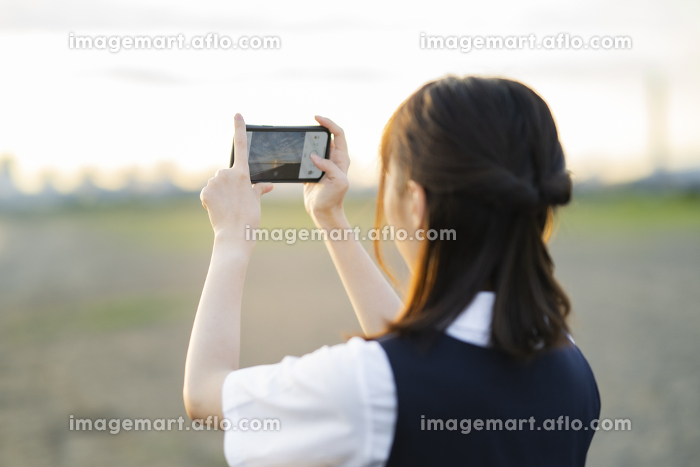 スマートフォンで景色を撮影するアジア人女性の高校生の販売画像