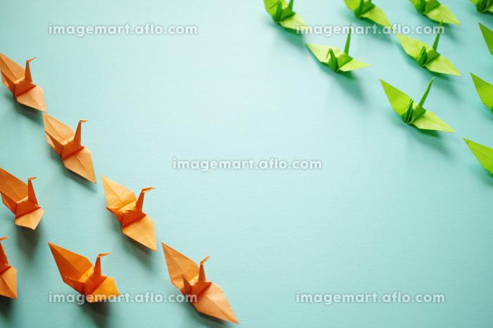 中央の空間を挟んで橙色と黄緑色の折り鶴の群れが対峙している。の販売画像