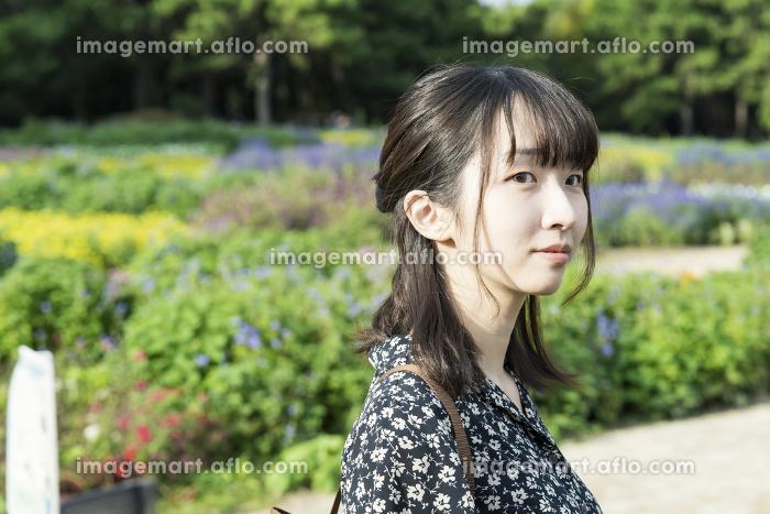 花畑を散歩するアジア人の若い女性の販売画像