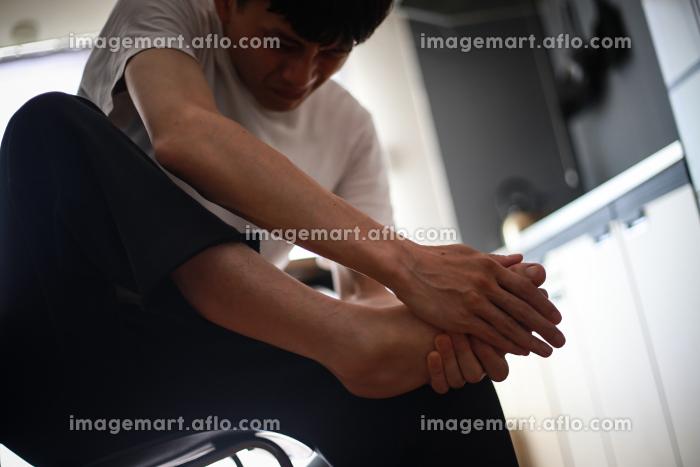足の痛みに悩む男性の販売画像
