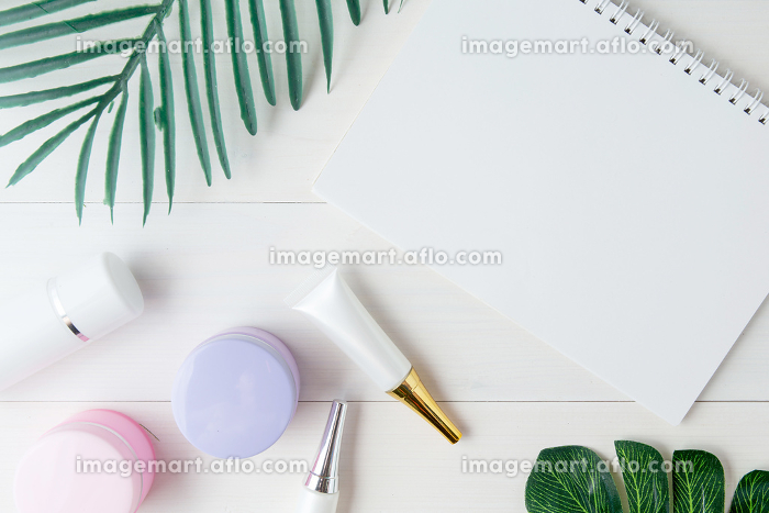 cosmetic and skin care product and notebook and leaves on table,の販売画像