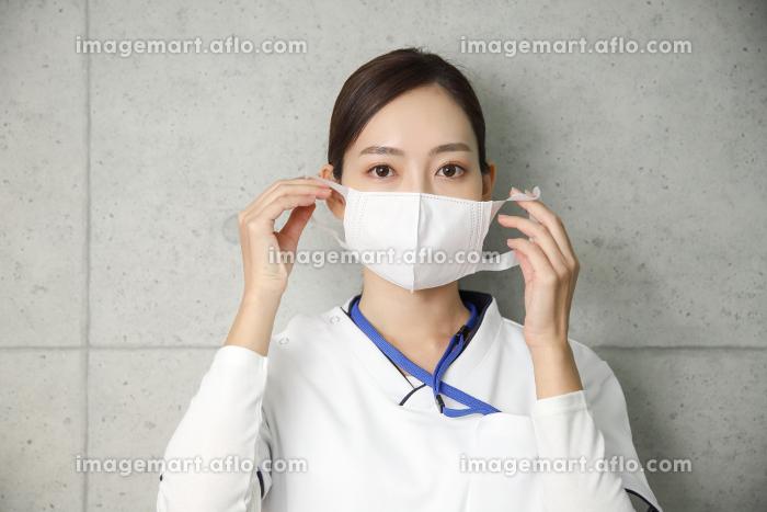 真剣な表情でマスクをつける医療従事者の女性の販売画像