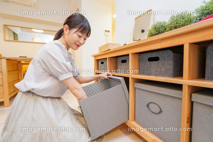 棚の片付けをする若い女性の販売画像