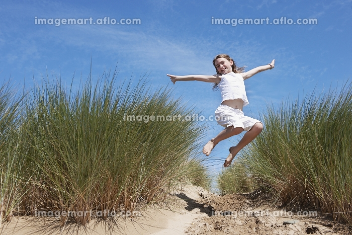 Young Girl Jumping in Sand dunesの販売画像