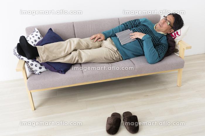 ソファでうたた寝するミドル男性の販売画像