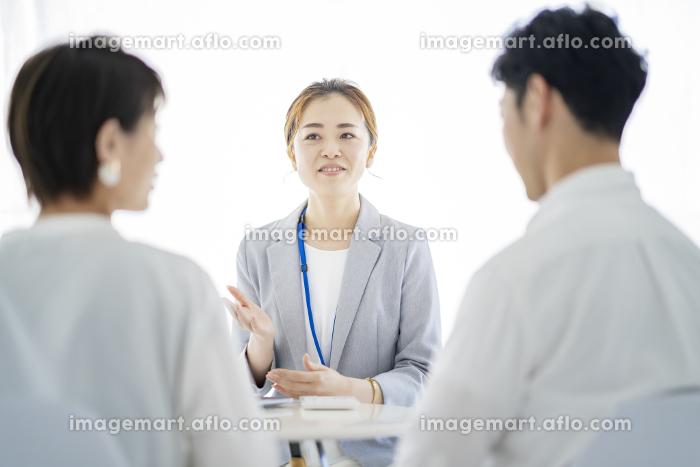 夫婦に説明するスーツ姿の女性の販売画像