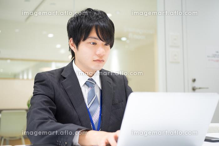 真剣な表情で仕事をする会社員(男性・電話・パソコン)の販売画像