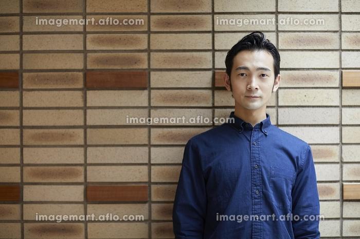 壁を背にした日本人男性のポートレートの販売画像
