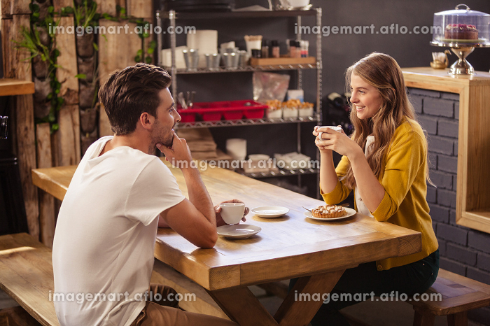Two smiling hipsters drinking coffeeの販売画像