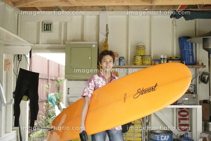 ガレージでサーフボードを持つ若者