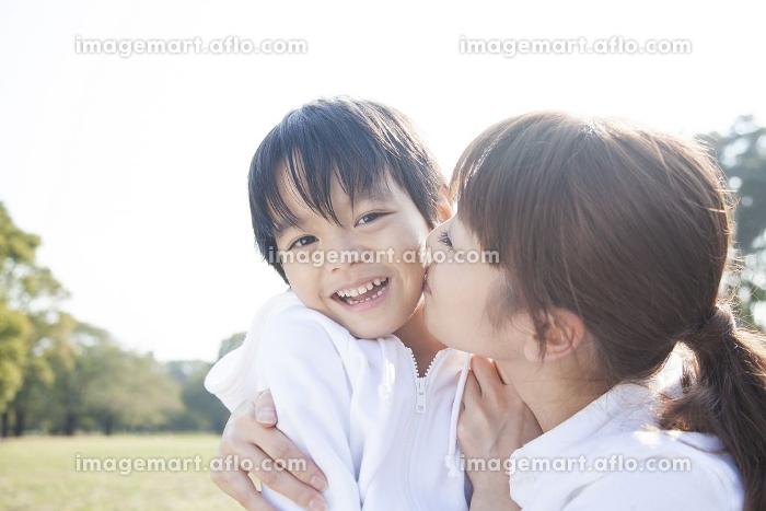 男児の頬にキスする母の販売画像