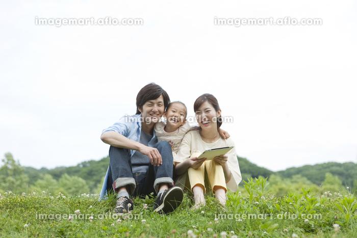 野原に座る家族3人の販売画像