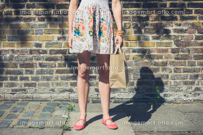 A young woman wearing a summer dress is standing in the street with a paper bag