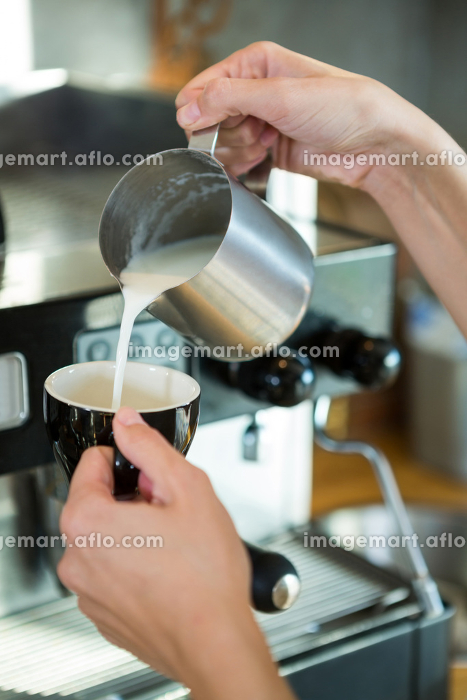 Waitress pouring milk in the cup
