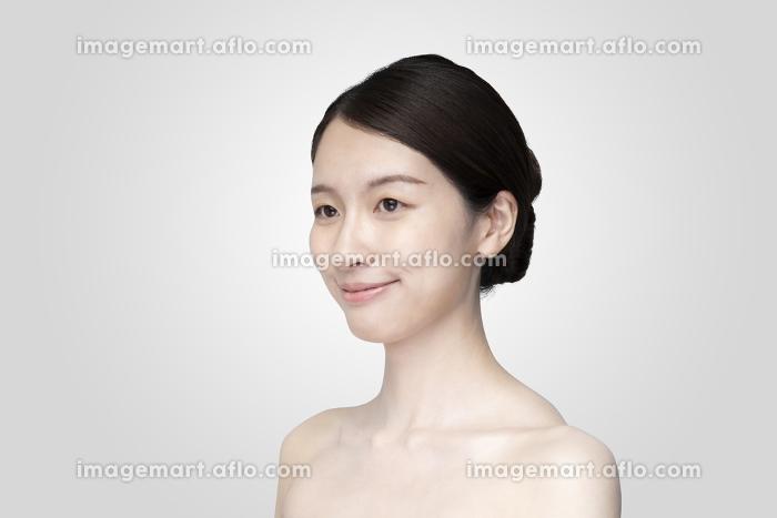 リラックスした表情で白い背景の前に立つ若い女性の販売画像