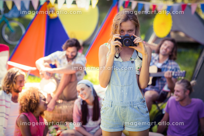 Portrait of woman taking a picture of friends at campsiteの販売画像
