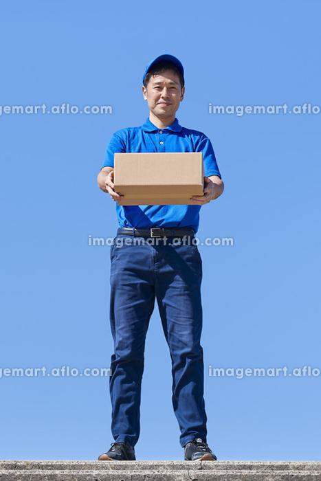 荷物を差し出す配達員の販売画像