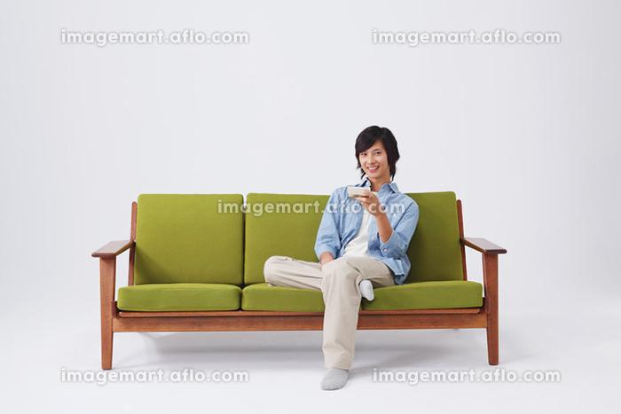 ソファでくつろぐ若者