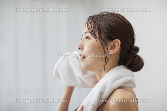 タオルで汗を拭く若い日本人女性の販売画像