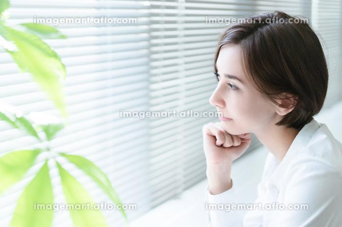 窓のブラインドから外を見つめる女性の販売画像