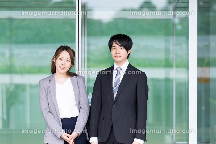 自動ドアの前に立つ男女(ビジネス・共働き・夫婦・同僚)の販売画像