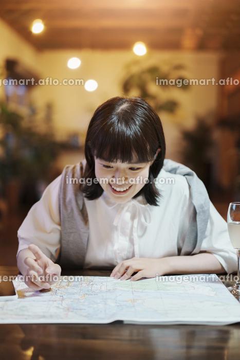 おしゃれな空間で、地図を見る若い女性の販売画像