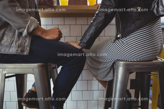 Low section of couple on stool in cafeの販売画像