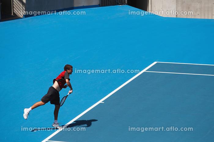 サーブを打つ男子テニス選手の販売画像