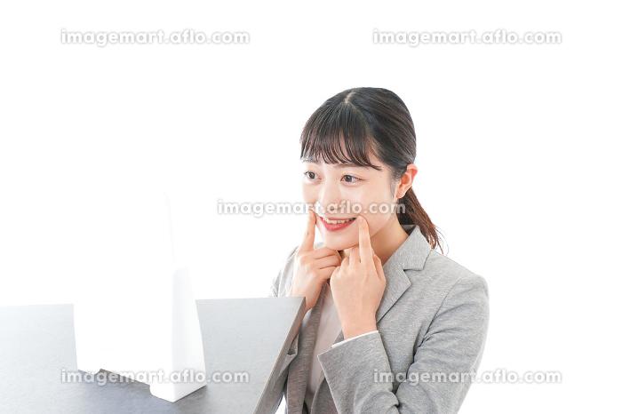 身だしなみを整えるビジネスウーマンの販売画像