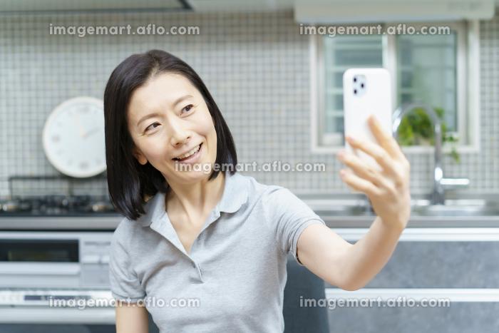 スマートフォンで自分を撮影するミドル女性の販売画像
