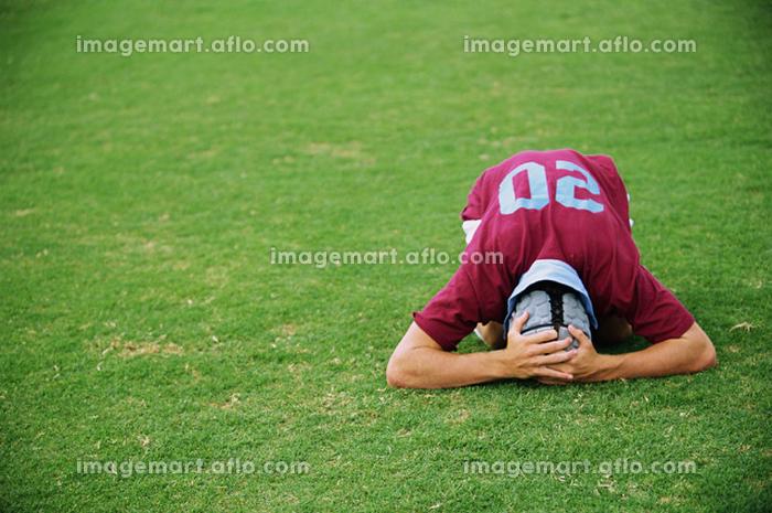 頭を抱えるラグビー選手の販売画像