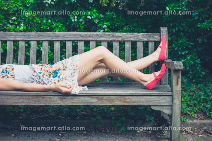 A young woman wearing a summer dress is relaxing on a bench in the park on a sunny dayの販売画像