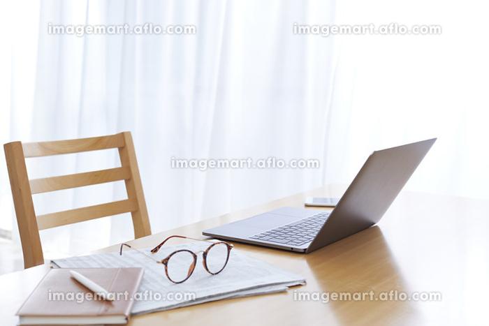 テーブル上のノートパソコンと眼鏡の販売画像