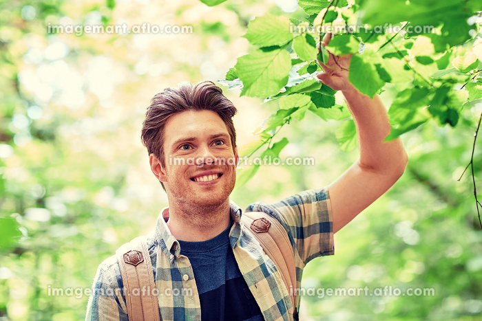 smiling young man with backpack hiking in woodsの販売画像
