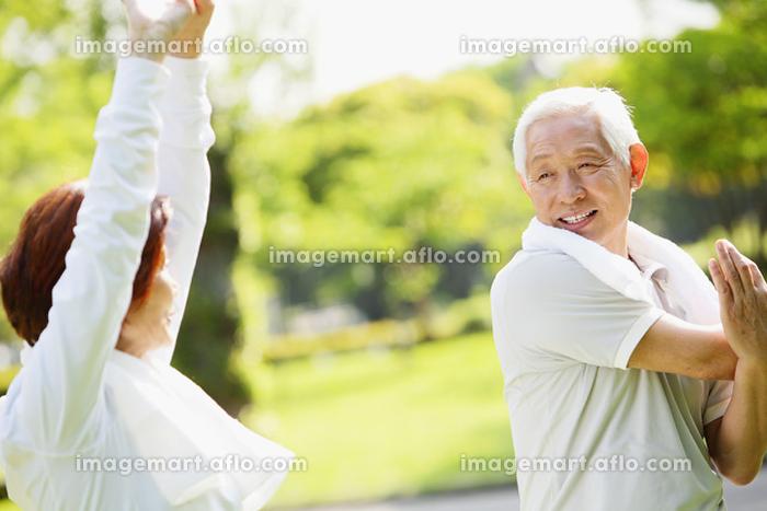新緑と柔軟体操するシニア夫婦の販売画像