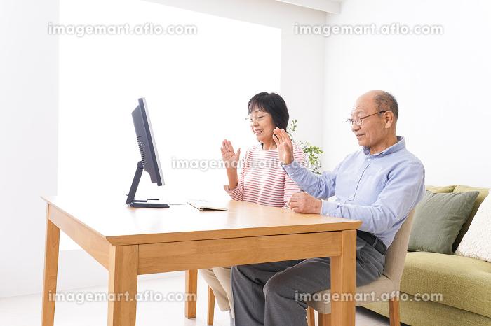 パソコンでテレビ電話をする高齢の夫婦の販売画像