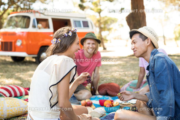 Friends looking at woman laughing while sitting on fieldの販売画像