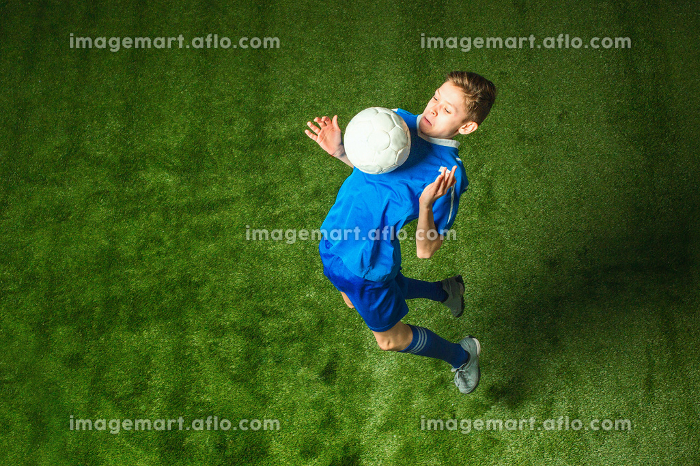 Young boy with soccer ball doing flying kickの販売画像