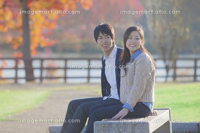 紅葉を眺めながら座るカップル