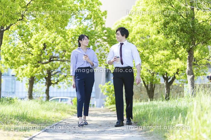 公園を歩く男女の販売画像