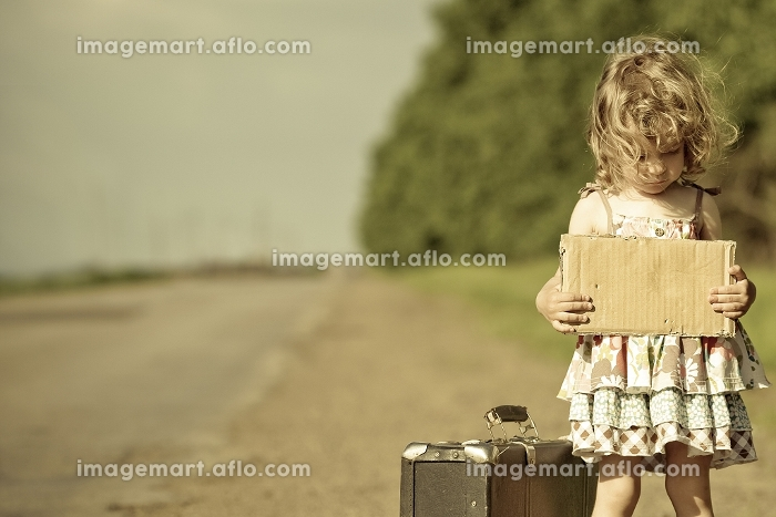 Lonely girl with suitcase standing about road and holding paper with copyspace in handsの販売画像