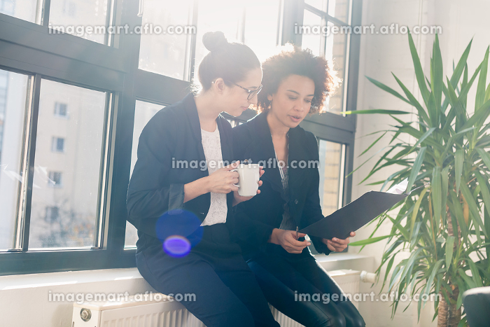 Two young colleagues reviewing business reports during breakの販売画像