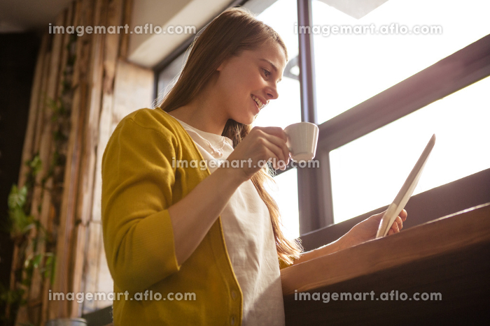Smiling woman drinking coffee and using tabletの販売画像